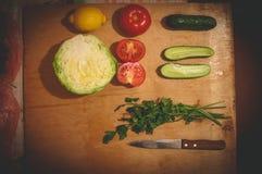 Verduras cortadas en el tablero de madera Col, tomates, pepinos, lim?n y perejil imagenes de archivo