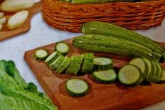 Verduras cortadas en un tablero de madera en un fondo blanco imagen de archivo