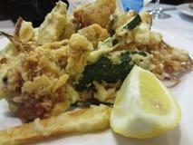 Verduras crujientes empanadas y fritas con la rebanada del limón Anillos de cebolla, calabacín, patatas y coliflores estropeados  Foto de archivo libre de regalías