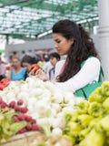 Verduras de compra de la mujer bastante joven en mercado fotos de archivo