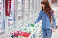 Verduras de compra de la mujer en la sección congelada imagenes de archivo