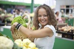 Verduras de compra de la mujer joven en el mercado del ultramarinos Imagen de archivo