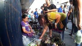 Verduras de compra de la gente del vendedor ambulante de la mujer a lo largo de la acera de la ciudad almacen de metraje de vídeo
