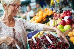 Verduras de compra de la mujer mayor en el mercado verde fotografía de archivo libre de regalías