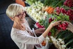 Verduras de compra de la mujer mayor en el mercado verde imagen de archivo libre de regalías