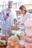 Verduras de compra y ultramarinos de los pares maduros en un mercado imágenes de archivo libres de regalías