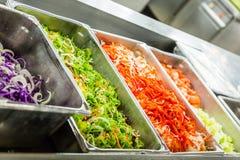 Verduras de ensalada en compartimientos de la porción Foto de archivo