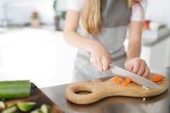 Verduras de un corte de la niña para la ensalada en la cocina Concepto de alimento sano fotos de archivo