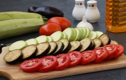 Verduras del corte: el calabacín, las berenjenas y los tomates están situados en un tablero de madera en un fondo oscuro imagen de archivo libre de regalías