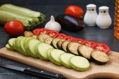 Verduras del corte: el calabacín, las berenjenas y los tomates están situados en un tablero de madera en un fondo oscuro fotos de archivo