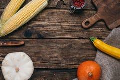 Verduras del otoño: calabazas y maíz con las hojas del amarillo y tablero cortado en un fondo de madera fotografía de archivo