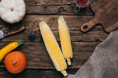Verduras del otoño: calabazas y maíz con las hojas del amarillo y tablero cortado en un fondo de madera foto de archivo libre de regalías