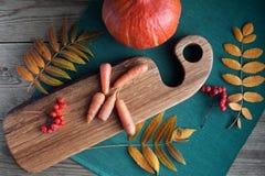 Verduras del otoño: calabazas y zanahoria con las hojas del amarillo y tablero cortado en un fondo de madera en cocina imágenes de archivo libres de regalías