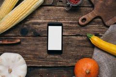 Verduras del otoño: el teléfono móvil con la pantalla, las calabazas y el maíz vacíos blancos con amarillo se va en un fondo de m fotografía de archivo