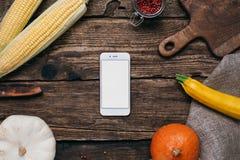 Verduras del otoño: el teléfono móvil con la pantalla, las calabazas y el maíz vacíos blancos con amarillo se va en un fondo de m fotos de archivo libres de regalías
