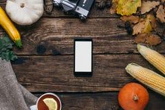 Verduras del otoño: el teléfono móvil con la pantalla, las calabazas y el maíz vacíos blancos con amarillo se va en un fondo de m imagen de archivo