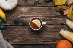 Verduras del otoño: té, calabazas y maíz con las hojas del amarillo en un fondo de madera fotos de archivo libres de regalías