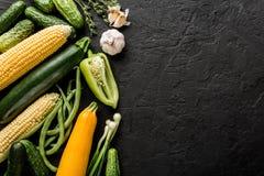 Verduras e hierbas crudas sanas, pepinos, maíz, pimienta, calabacín, habas verdes del vegano del verano en fondo de piedra negro imágenes de archivo libres de regalías