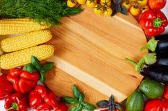 Verduras e hierbas orgánicas frescas alrededor del tablero de madera: paprika, mazorcas de maíz, aguacate, berenjenas, tomates de fotografía de archivo libre de regalías