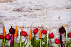 Verduras en el escritorio blanco viejo: zanahoria de bebé, ajo, remolacha, rábanos Fotos de archivo libres de regalías