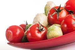 Verduras en la placa roja Imágenes de archivo libres de regalías