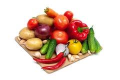 Verduras en una tabla de cortar en el fondo blanco Fotografía de archivo libre de regalías