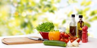 Verduras, especias y artículos de cocina en la tabla Imagenes de archivo