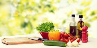 Verduras, especias y artículos de cocina en la tabla Imágenes de archivo libres de regalías