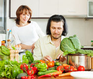 Verduras felices del corte de los pares en cocina Fotografía de archivo libre de regalías