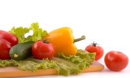 Verduras frescas a bordo en el fondo blanco Foto de archivo libre de regalías