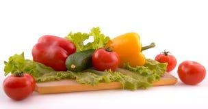 Verduras frescas a bordo en el fondo blanco Fotos de archivo libres de regalías