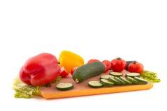 Verduras frescas a bordo en el fondo blanco Fotografía de archivo