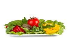 Verduras frescas coloridas en una placa, aislada en blanco fotos de archivo libres de regalías