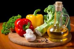 Verduras frescas con aceite en tabla de cortar Imágenes de archivo libres de regalías
