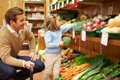 Verduras frescas de And Daughter Choosing del padre en tienda de la granja Foto de archivo libre de regalías
