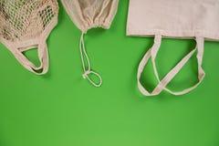 Verduras frescas en bio bolsos del algod?n del eco en fondo verde Concepto in?til cero de las compras imagen de archivo
