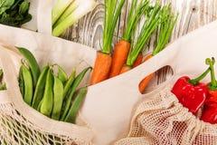 Verduras frescas en bio bolsos del algod?n del eco en la tabla de madera vieja foto de archivo libre de regalías