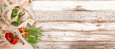 Verduras frescas en bio bolsos del algod?n del eco en la tabla de madera vieja imagen de archivo libre de regalías