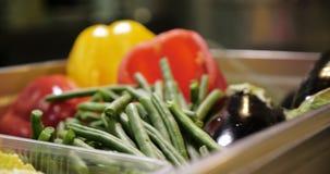 Verduras frescas en el vector Habas verdes y pimienta roja y calabaza en la tabla almacen de metraje de vídeo