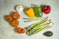 Verduras frescas en la tabla, tomates, ajo, espárrago, aguacate Imagen de archivo