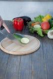 Verduras frescas en la tajadera y la tabla oscura Calabacín cortado en pedazos, sobre una tabla de madera hecha una composición d Imagen de archivo