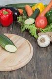 Verduras frescas en la tajadera y la tabla oscura Calabacín cortado en pedazos, sobre una tabla de madera hecha una composición d Imagenes de archivo