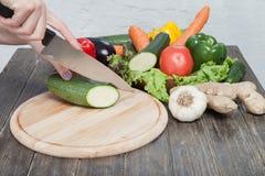 Verduras frescas en la tajadera y la tabla oscura Calabacín cortado en pedazos, sobre una tabla de madera hecha una composición d Fotografía de archivo