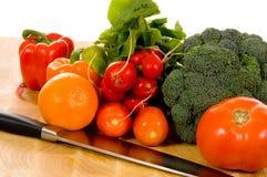 Verduras frescas en la tarjeta de corte con el cuchillo Imágenes de archivo libres de regalías
