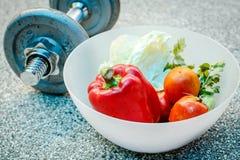 Verduras frescas en un cuenco y pesas de gimnasia Imagen de archivo