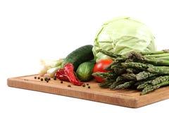 Verduras frescas en una tarjeta de corte de madera Imagenes de archivo