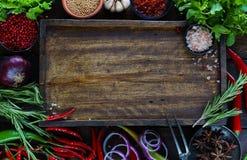 Verduras frescas, especias e hierbas en la tabla de madera y la tabla de cortar vacía Foto de archivo libre de regalías