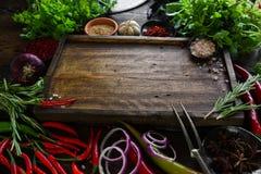 Verduras frescas, especias e hierbas en la tabla de madera y la tabla de cortar vacía Fotografía de archivo libre de regalías