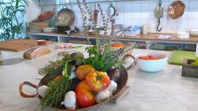 Verduras frescas, orgánicas, tomates, berenjenas, ajo e hierbas, en un cuenco en una tabla de cocina fotos de archivo libres de regalías