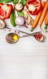Verduras frescas para cocinar sano con las cucharas, el aceite y las especias en el fondo de madera ligero, visión superior Imagenes de archivo